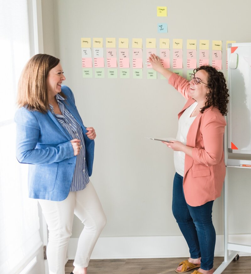 Nashville business owners pointing at a wall with sticky notes in pink and blue blazers