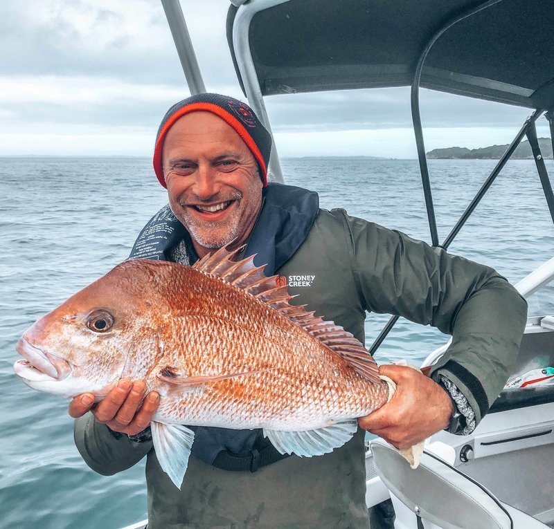 Warren holding the snapper he caught on north island fishing trip, new zealand