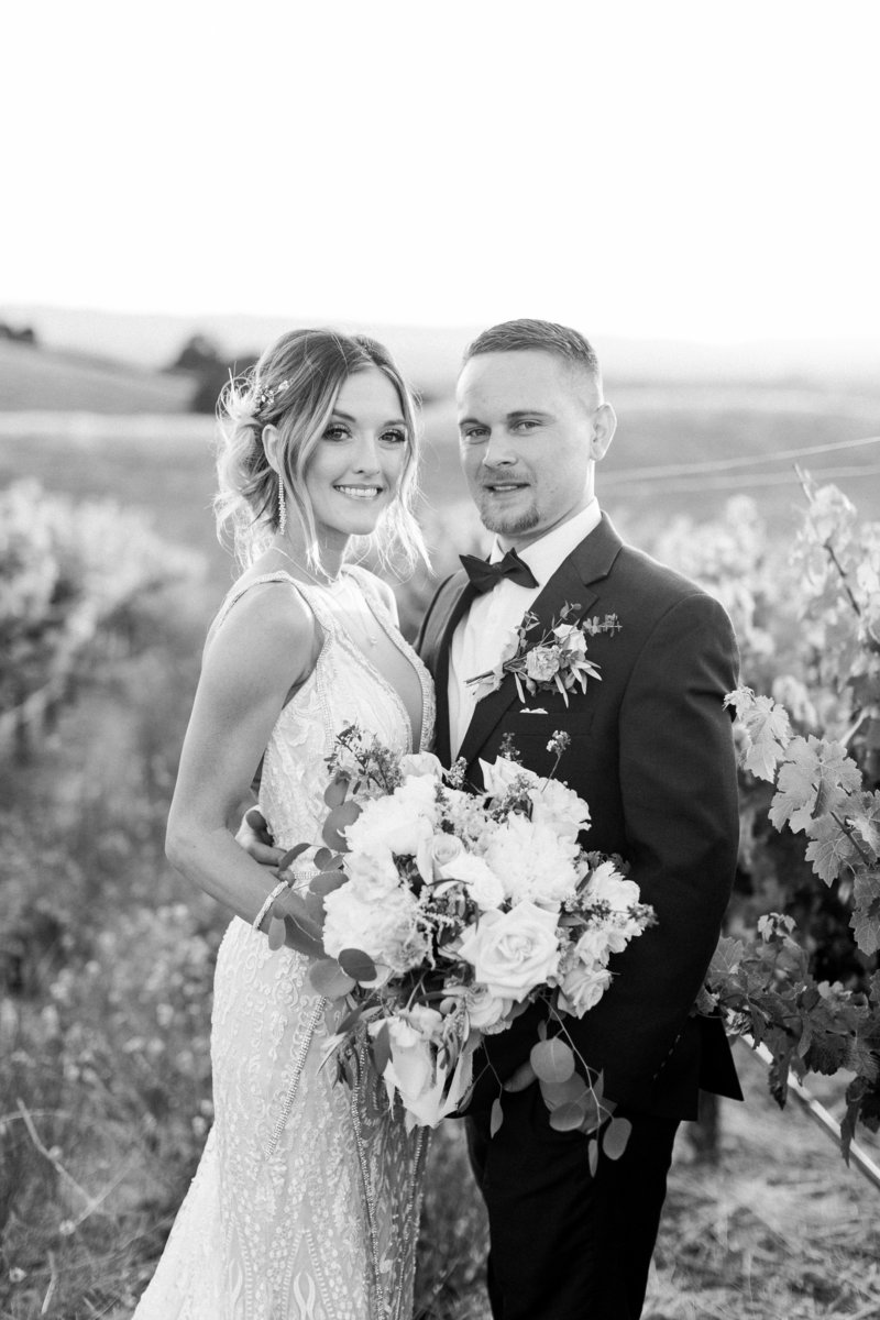 Bride and groom smiling in the vineyards at their Livermore wedding at Murrieta's Well