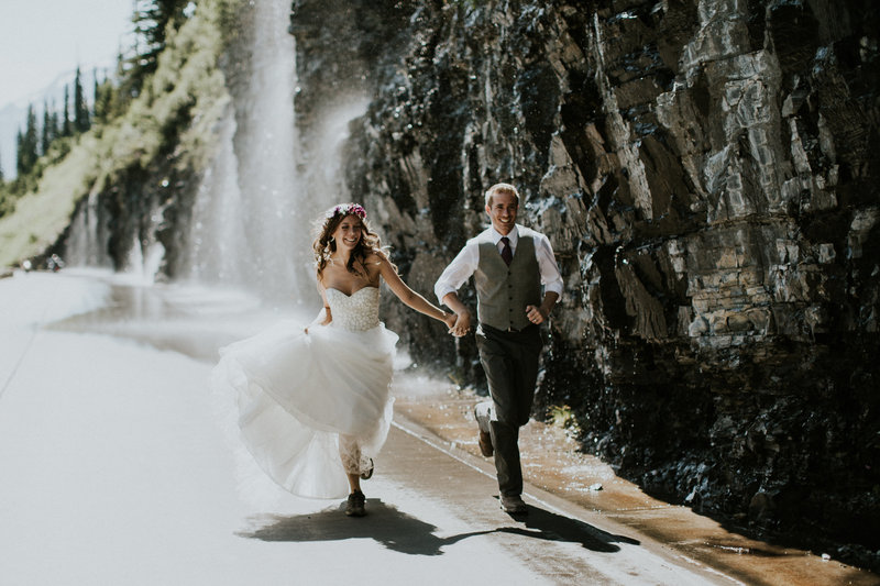 Glacier National Park Weeping Wall Elopement Couple Running under Waterfall