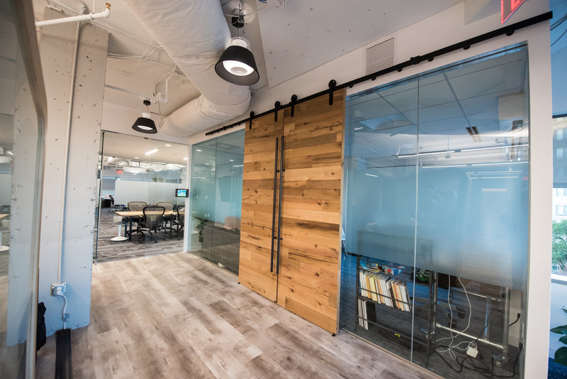 Wooden doors open conference room with glass walls.