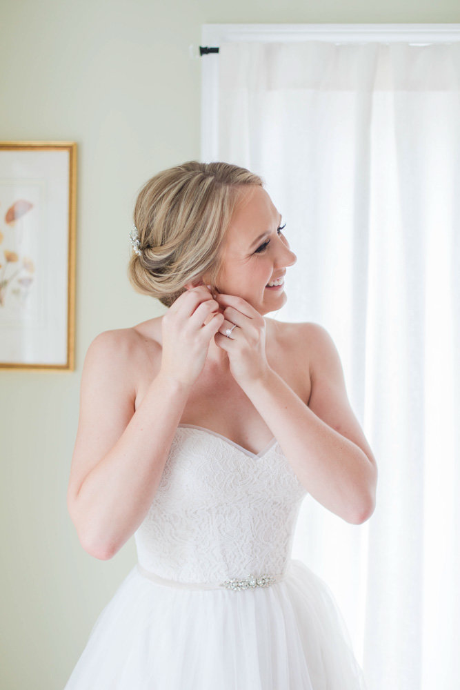 bride putting on earrings at eastern shore wedding at kirkland manor by costola photography
