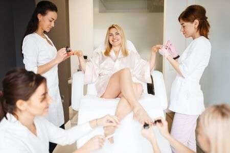135594447-four-masters-and-one-woman-pedicure-and-manicure