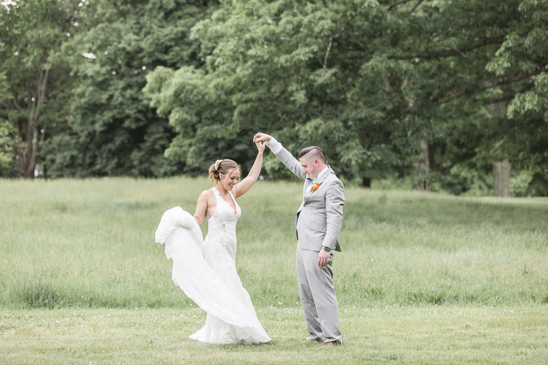 Groom dancing with bride in a field