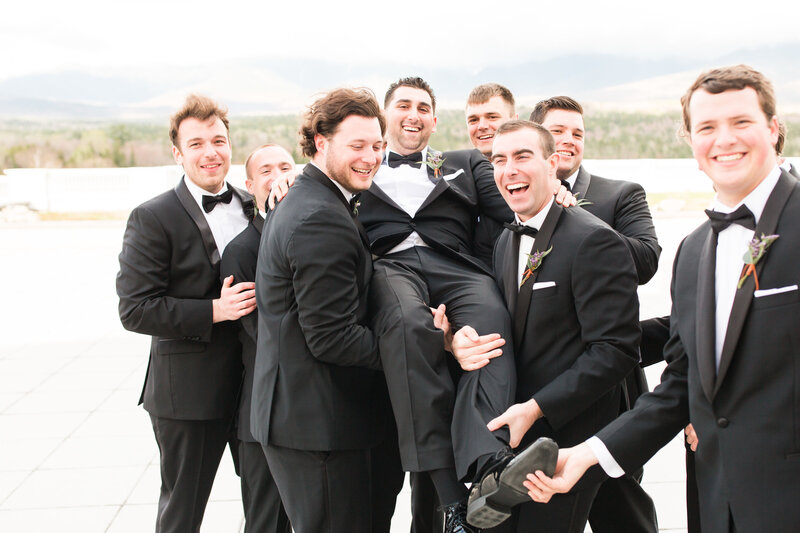 groom being held by groomsmen
