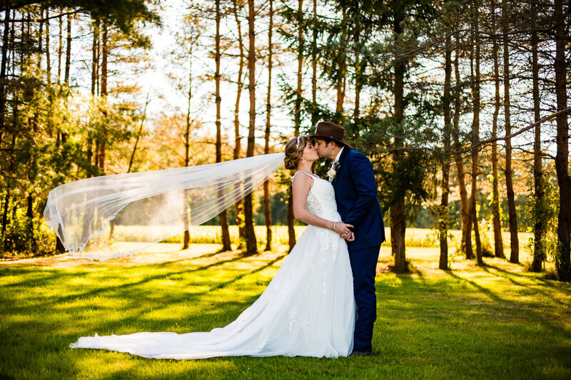 Bride and groom kiss as veil flies up on family farm in Watreford PA