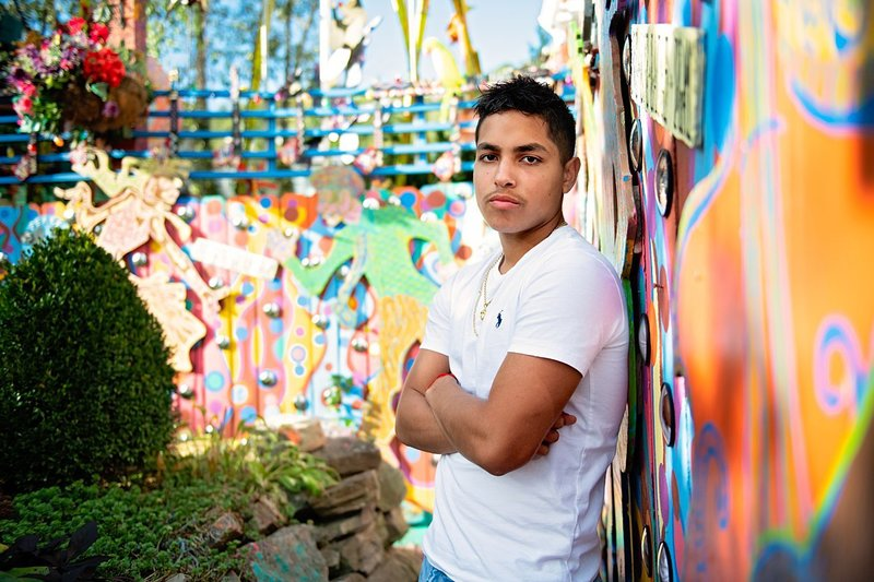 High school senior boy in white Polo tee and jeans leaning on colorful wall at Randyland in Pittsburgh, PA