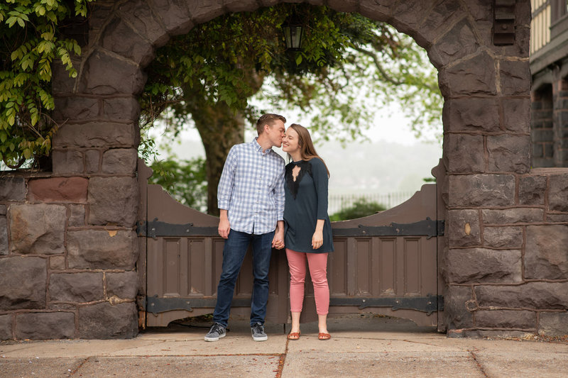Husband kissing wife's cheek framed in brownstone archway with gate