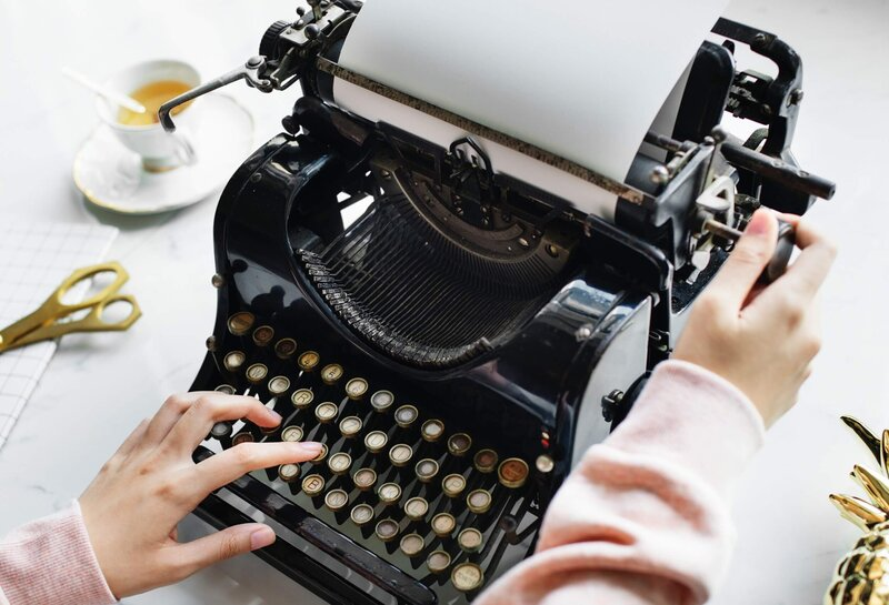 Old fashioned typewriter with woman typing on it