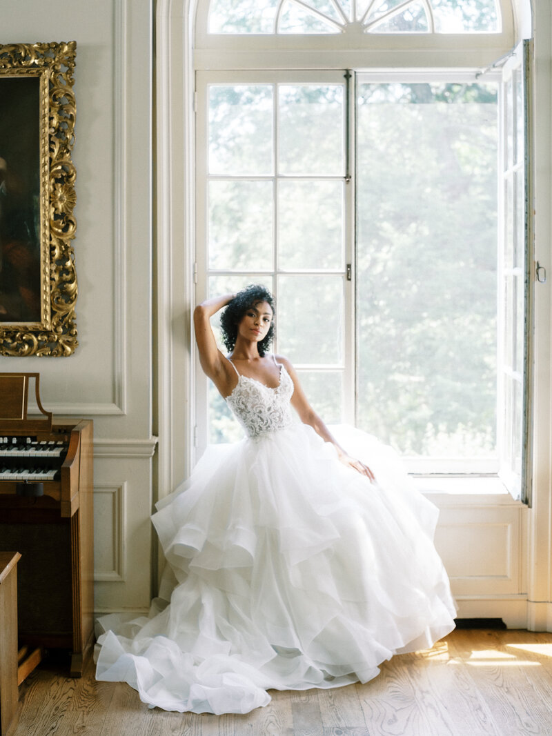 Bride sitting in mansion window for editorial photography