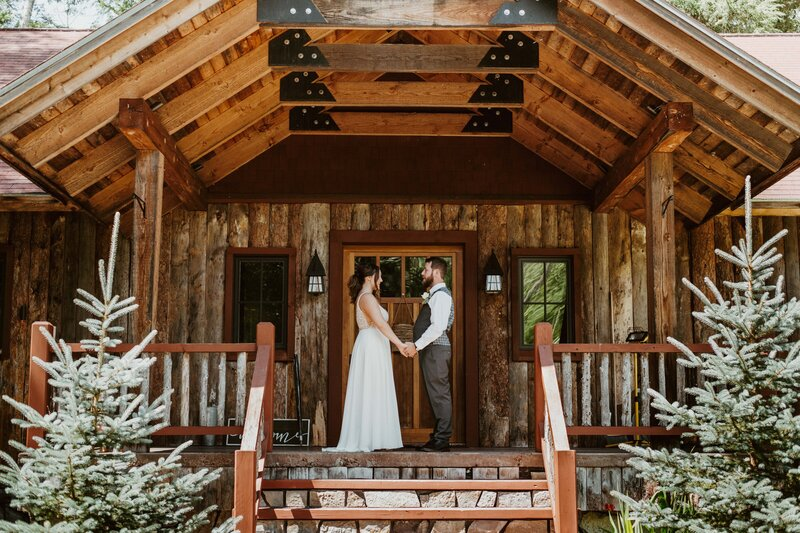 bride and groom holding hands in front of an A-frame cabin