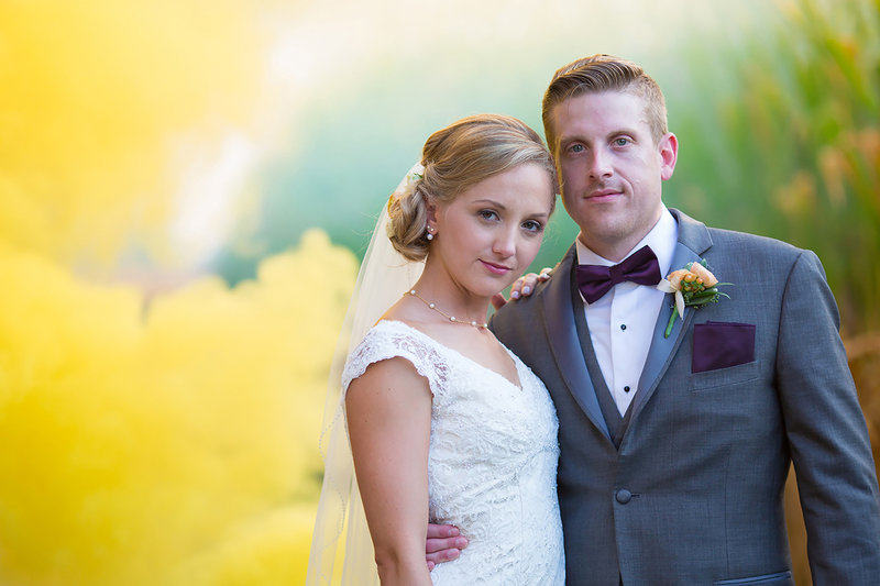 Colorful, bold photo of bride and groom standing in front of a  cornfield with yellow  smoke bombs filling the air with a pastel yellow colored smoke with the couple looking very stoic . Captured by DC wedding photographer Lee Hickman