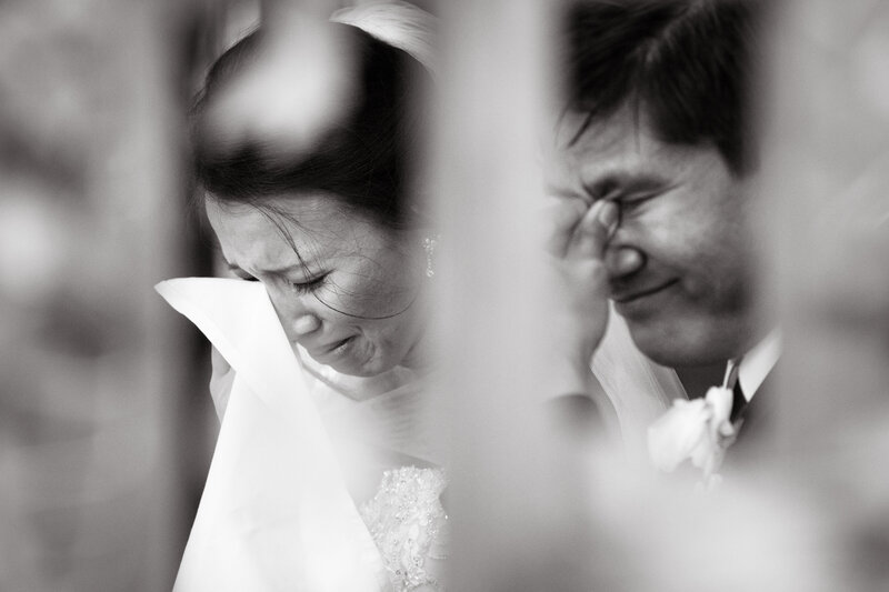 A candid emotional moment of both bride and groom crying.