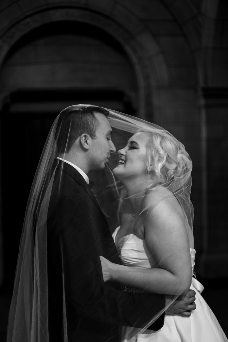 Bride and groom laugh under bride's veil inside the Cathedral of Learning in Pittsburgh PA