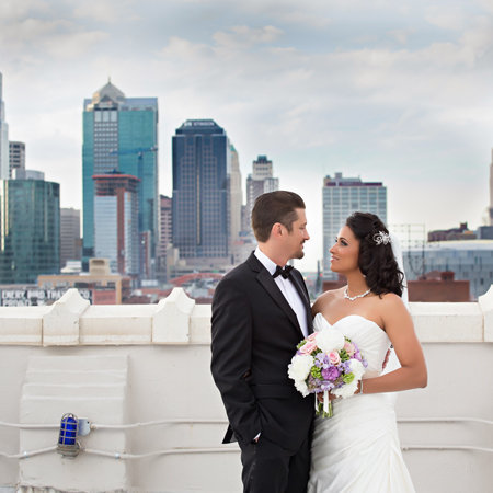 Beautiful couple standing in front of the  Kansas City Skyline writes wedding review  for their photographers
