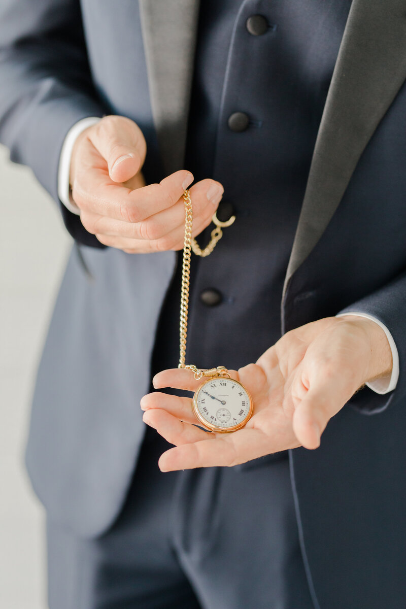 groom holding old watch at Inn at Perry Cabin wedding in St Michaels Maryland by Costola Photography