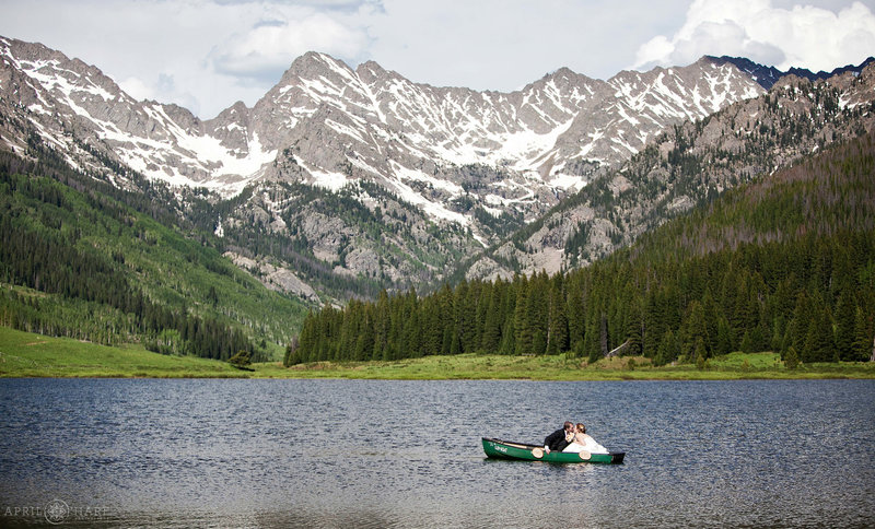 Bride and Groom kiss in the canoe with stunning mountain views at Piney Lake
