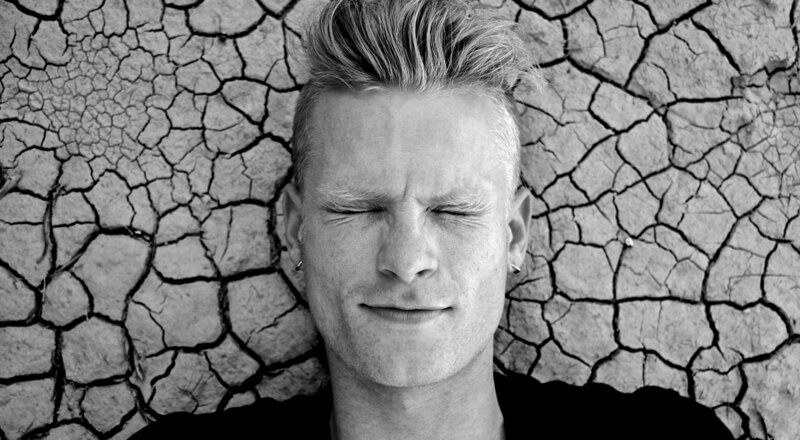 Music portrait Ryan Guldemon lying on cracked desert ground close up eyes closed black and white