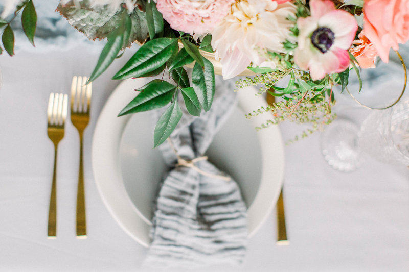 plate and gold forks laying on  table with flowers