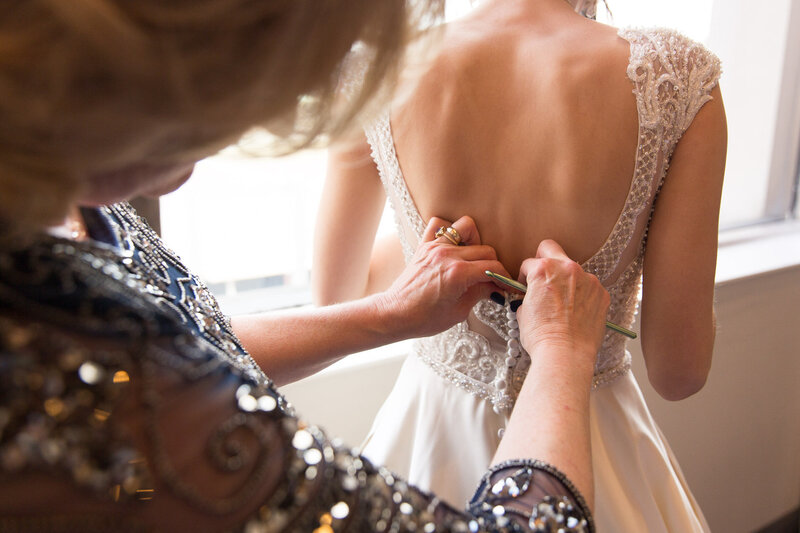 mom buttoning bride's dress at cityflats ballroom port huron