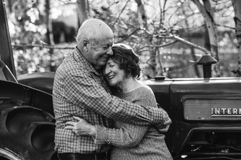 elderly couple embraces in front of vintage tractor