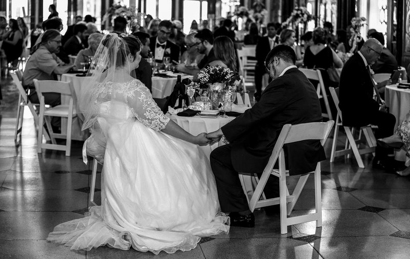 Bride and groom hold hands during prayer at a Warner Theatre wedding reception