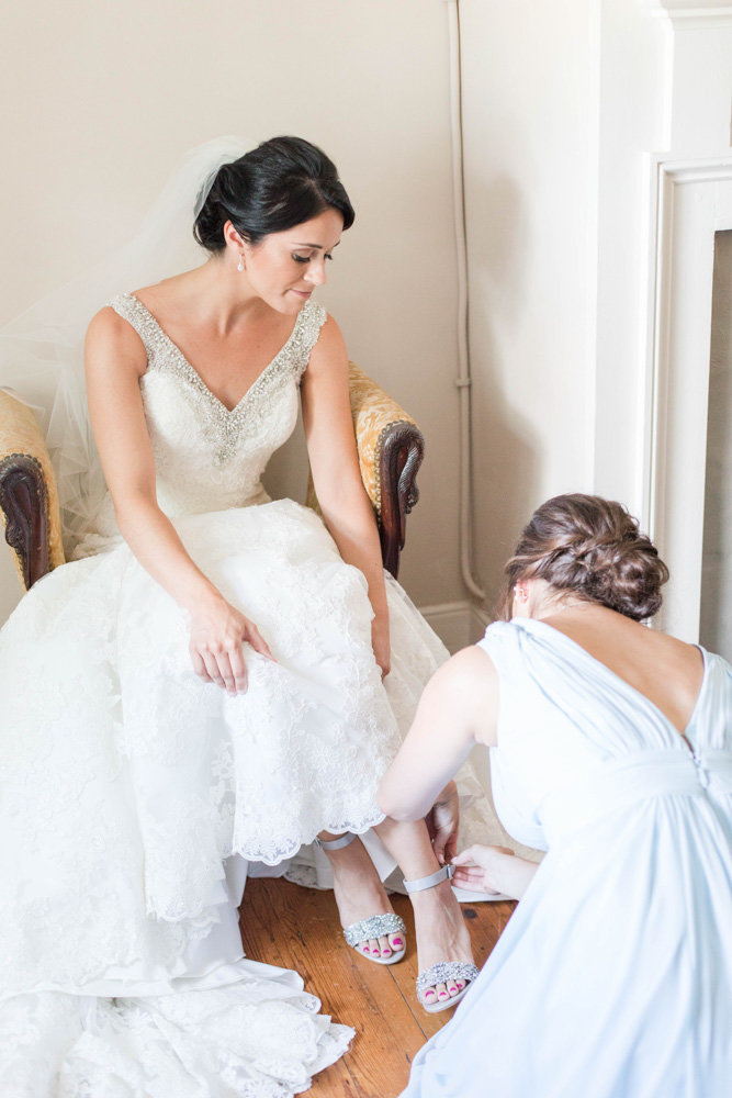 bride putting on shoes at springfield manor winery and distillery wedding by costola photography