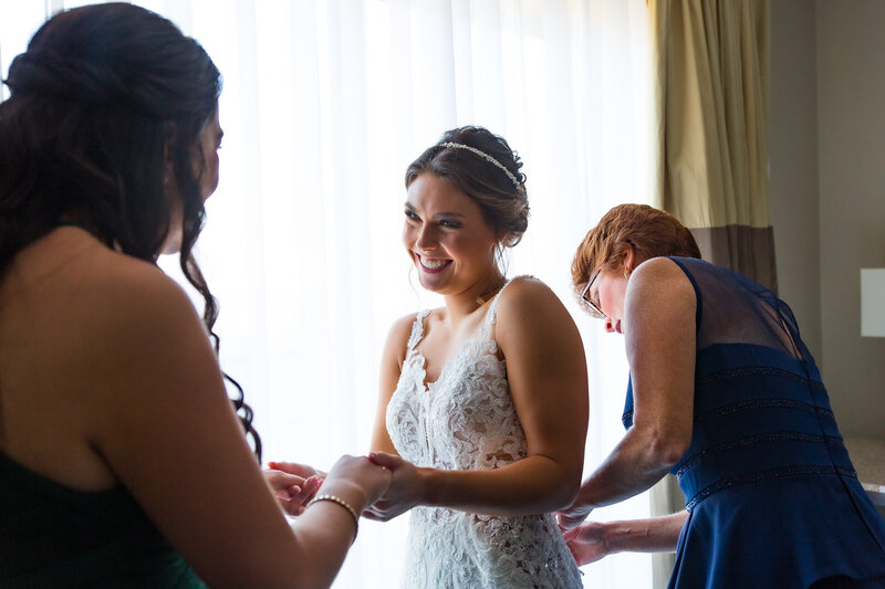 mother of the bride buttoning up bride's dress on morning of wedding day