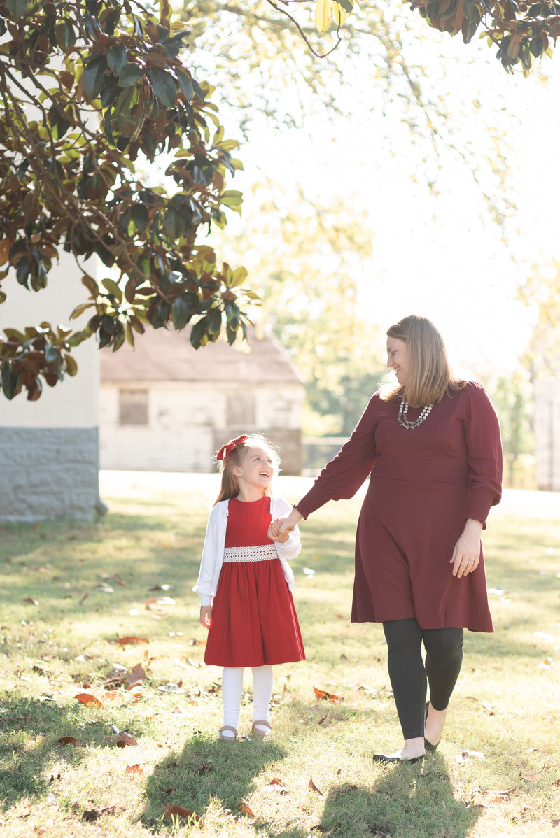 A daughter wearing a red dress is holding her mother's hand and walking towards the camera and smiling at eachother in Nashville