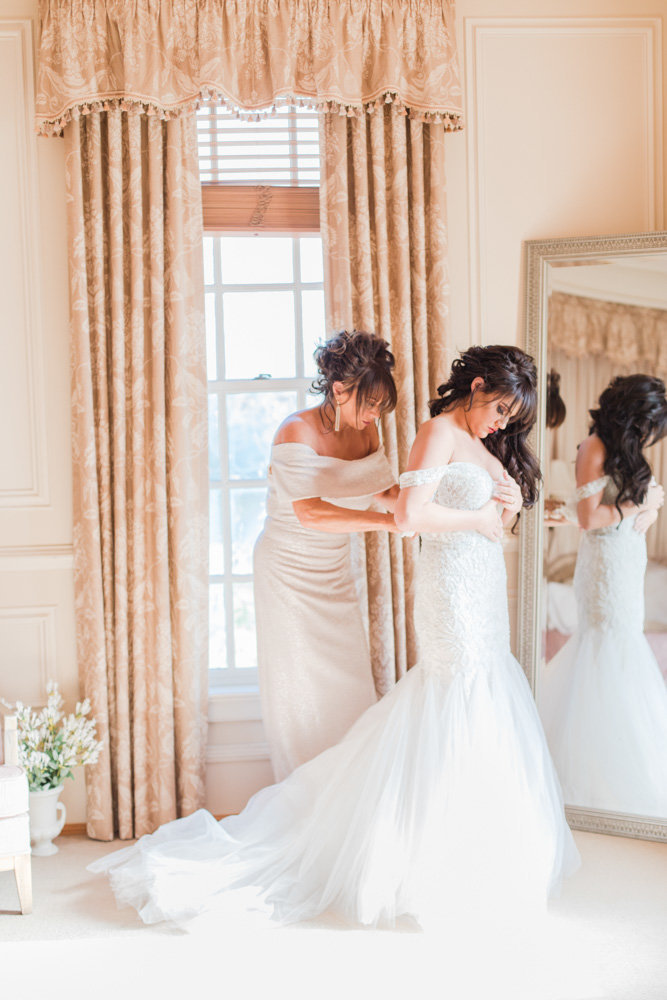 bride getting into dress in bridal suite at great marsh estate wedding in northern virginia by costola photography