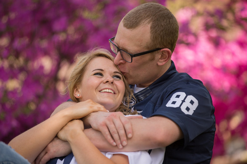 Man kisses the top of fiancee's head during Penn State Erie engagement session