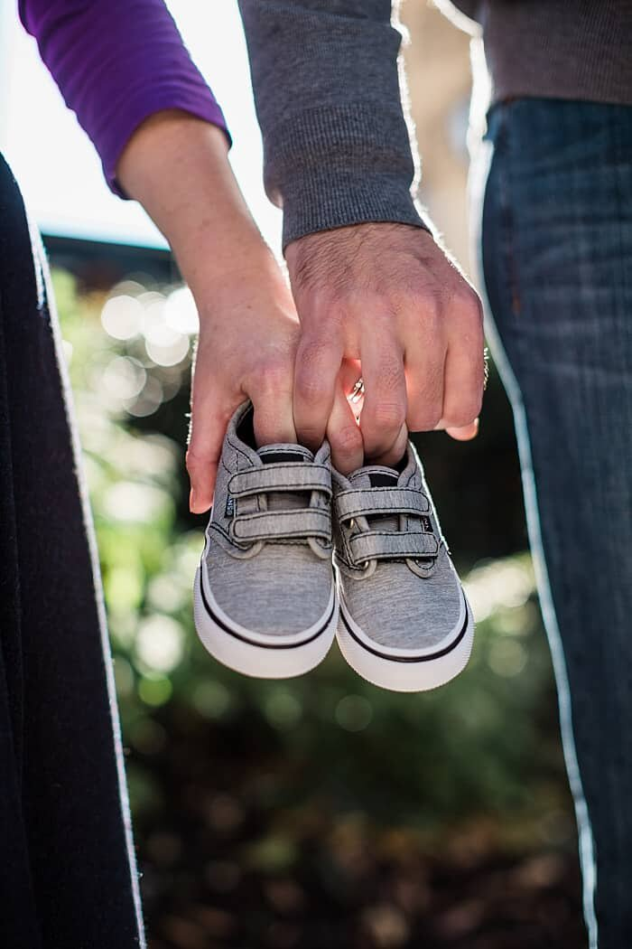 pregnancy announcement with mom and dad holding baby shoes