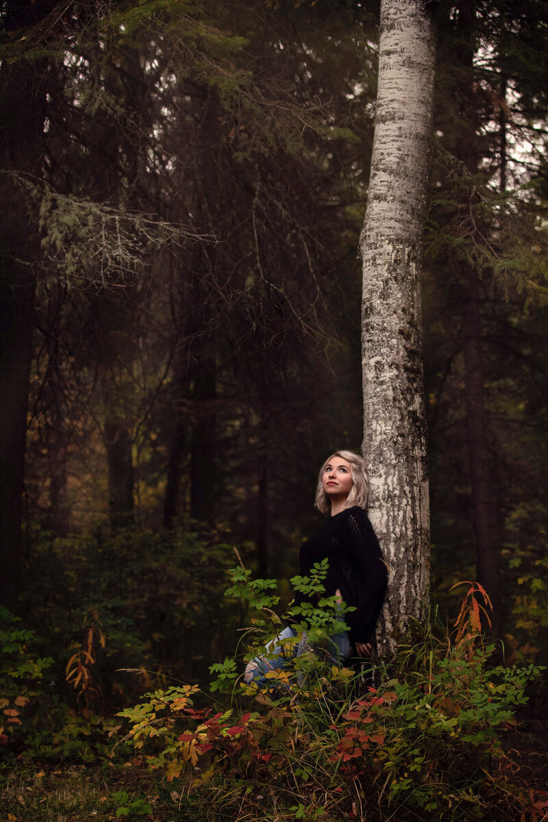 blonde girl leans on tree in the forest