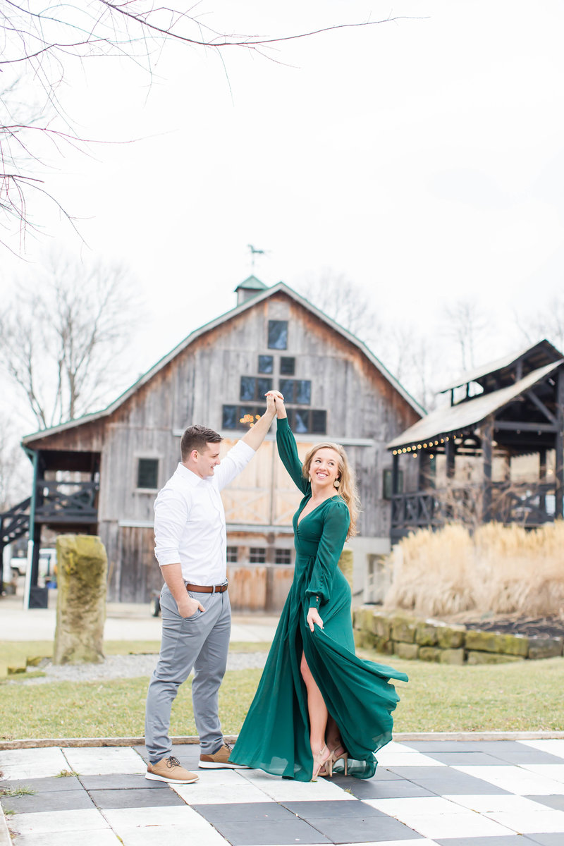 Bride in a green dress touching her nose to her fiance at their winter engagement photos at Rivercrest Farm photographed by akron ohio wedding photographer
