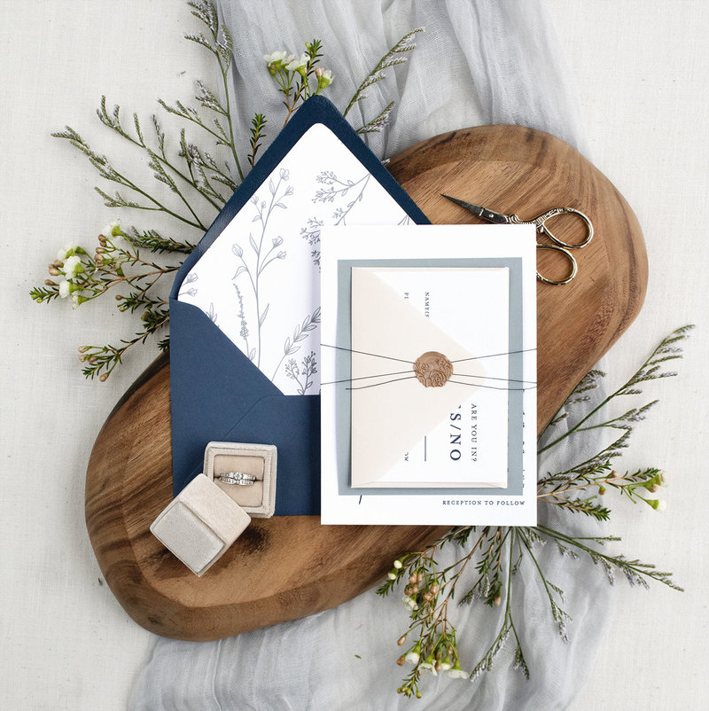 Modern Wildflower Invitation shown with a wax seal and lovely illustrated envelope liner // blue and navy accents.