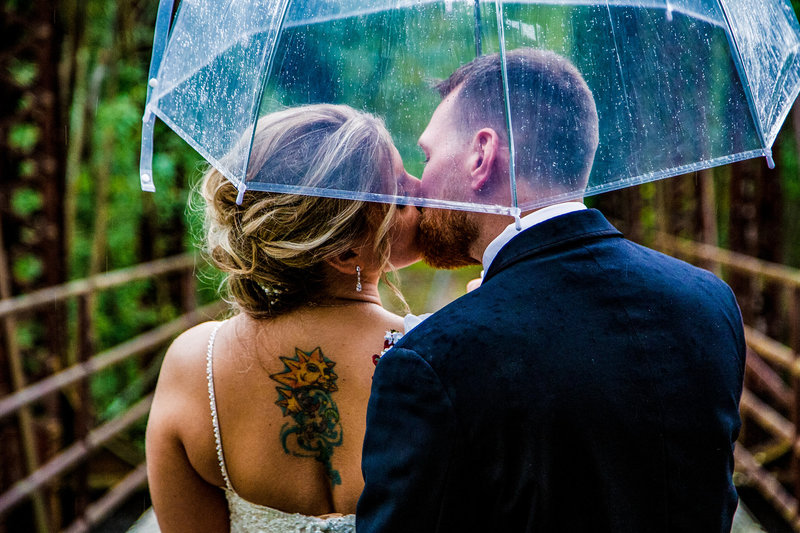 Bride and groom kissing under an umbrella on the train trestle at Barn at Conneaut Creek