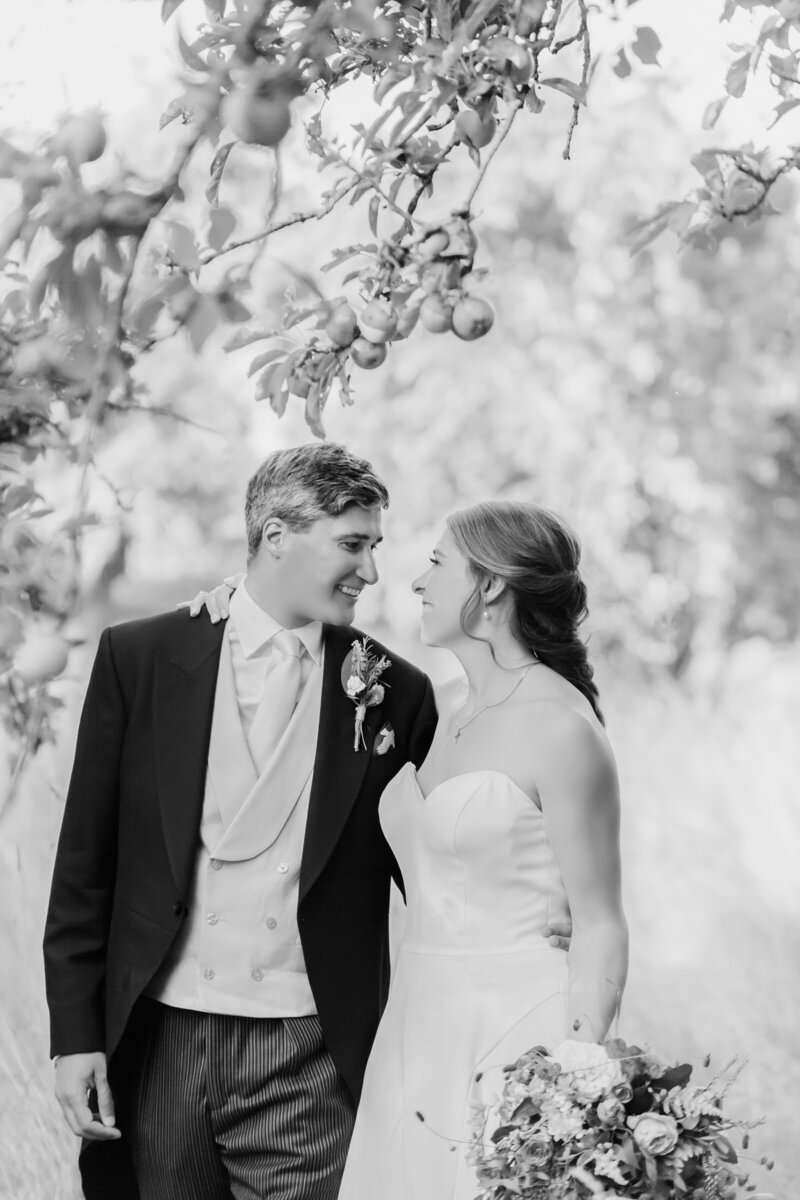 Bride and Groom walk through the apple orchard of private estate
