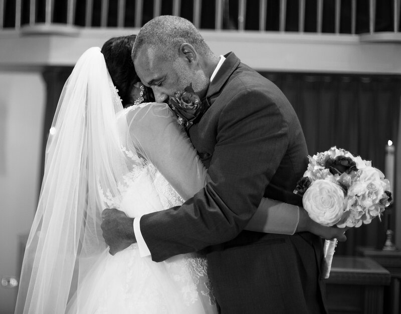 Bride hugs her father in between formal family portraits in church after wedding ceremony