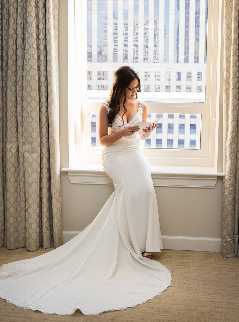 bride reading letter from groom on window ledge of hotel room at the NOPSI New Orleans hotel