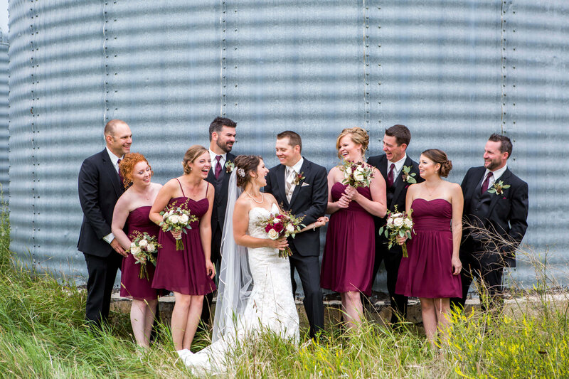 large wedding party laughing in front of grain bin