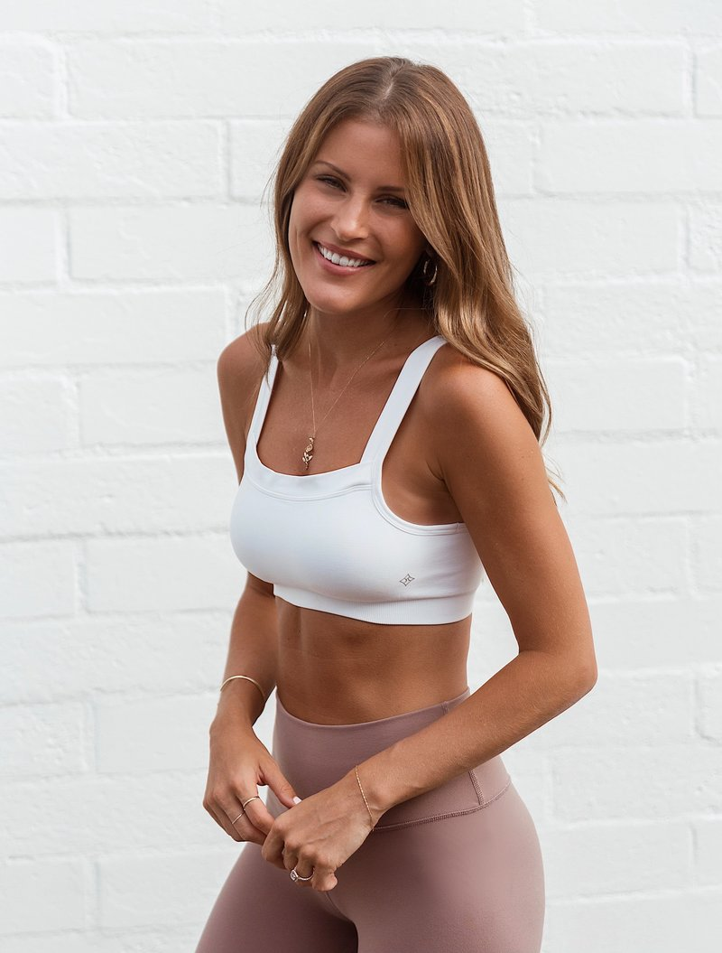 Lindsay Marcella smiling in athletic attire in front of a white wall