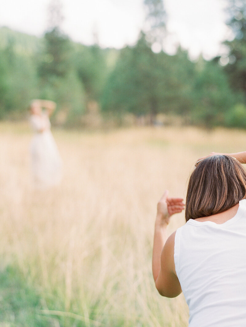 Wedding photographer guides bride posing in outdoor field