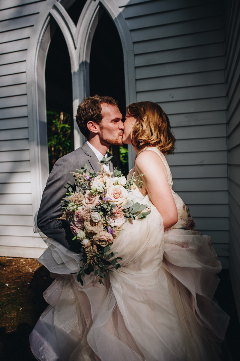 A bride and groom share a kiss outside the chapel