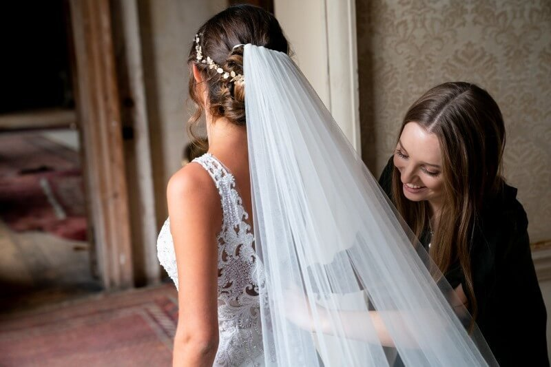 Rachel helping bride with dress | Wedding Planner Hampshire, Dorset, Surrey