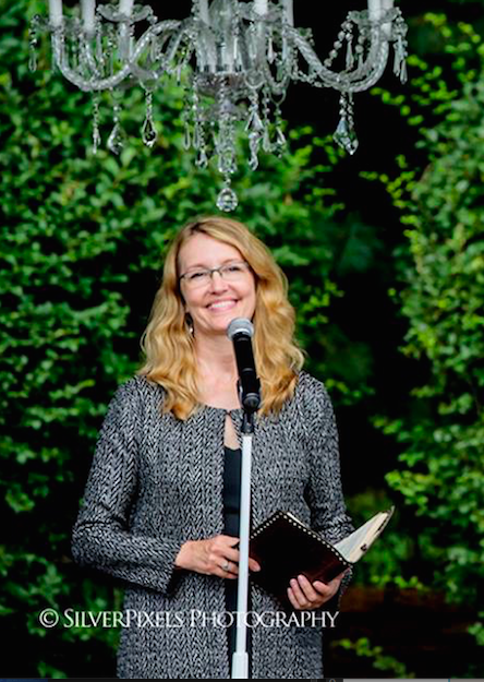 Donna Forsythe, owner of Lehigh Valley Celebrants, is  officiating a wedding at Pen Ryn Estate. She is standing at the ceremony space under a crystal chandelier, watching the bride walk down the aisle.