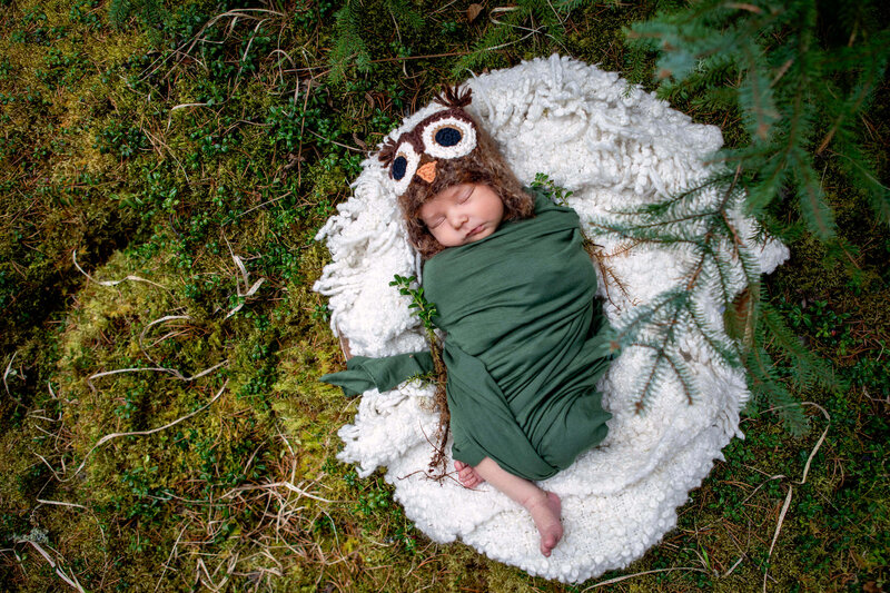 newborn boy with owl hat nestled in moss