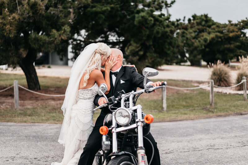 bride and groom kissing on a motorcycle in duck, nc