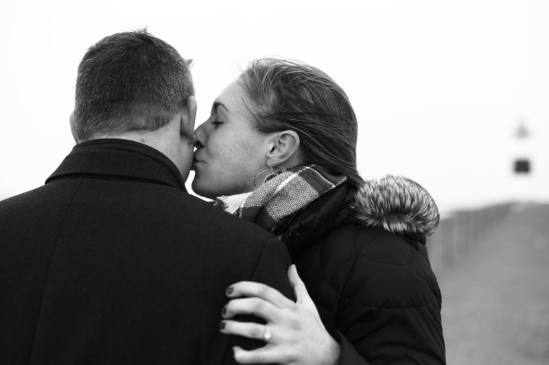 Woman kisses fiance's cheek on the North Pier during winter engagement portrait session