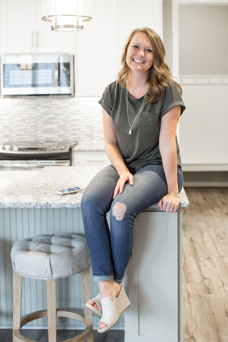 Jess sitting on a new counter top in a house she just sold to a first time home buyer.