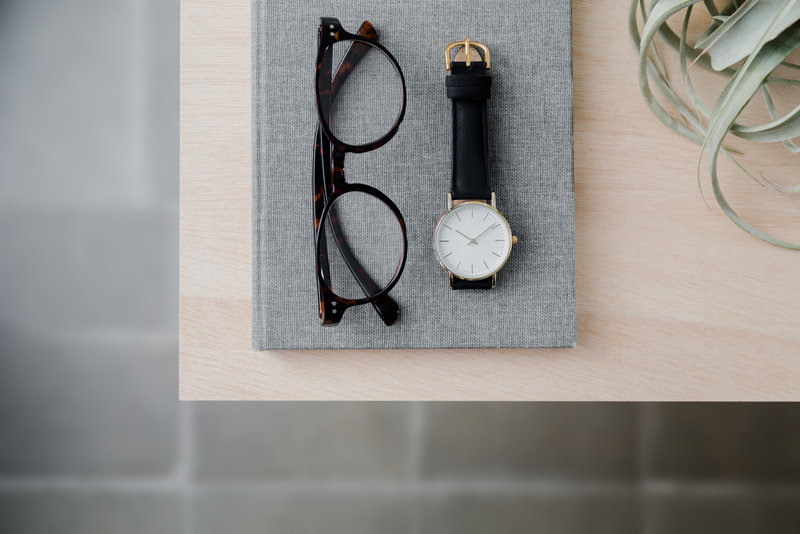 Branding price | Top view composition of a notebook, reading glasses, watch and plant